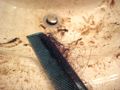 comb full of hair sitting on a dirty sink
