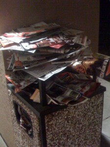 outdoor trash can overflowing with junk mail