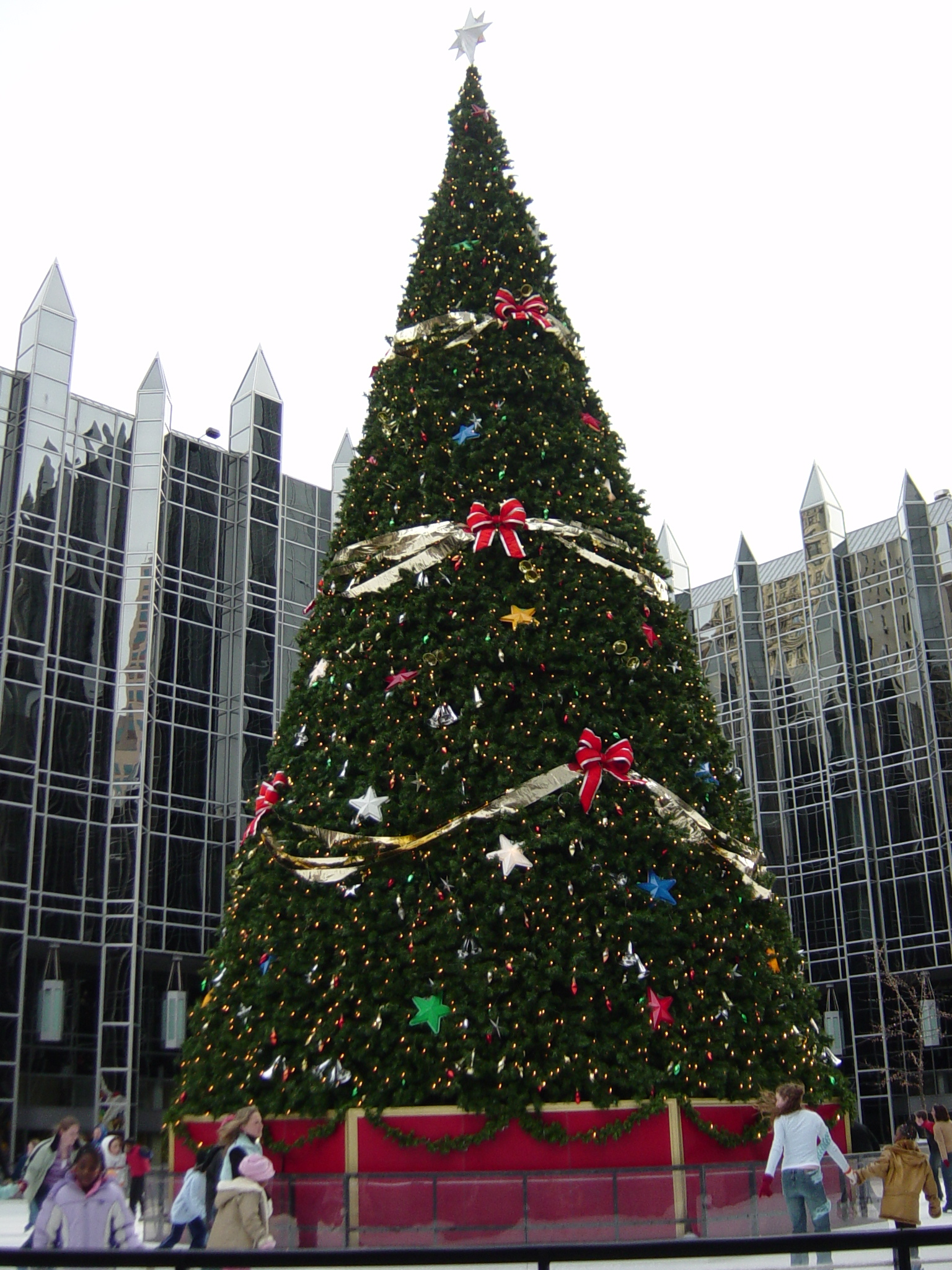 Large Outdoor Christmas Tree With Ice Skaters Skating Around It