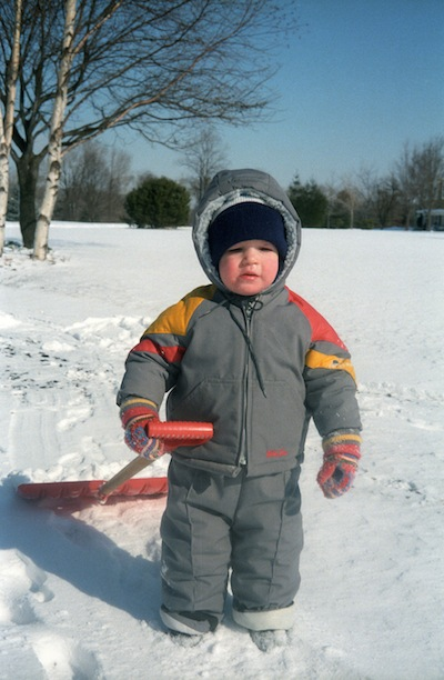 Michael Wyszomierski in a snowsuit holding a shovel