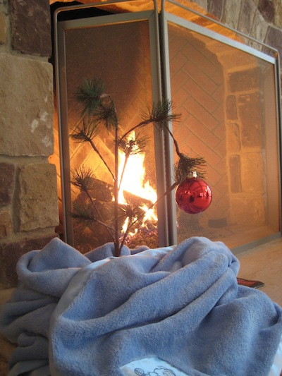 charlie brown tree with blue blanket around bottom by fireplace
