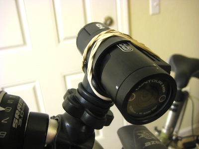alternate view of camera on handlebar with rubber bands holding it on