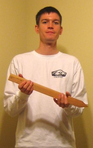Michael Wyszomierski holding a wooden stake.