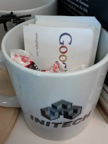 Tootsie Rolls in an Initech mug with Google business cards