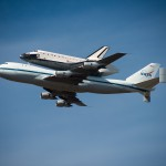 Space Shuttle Endeavour on top of NASA's Shuttle Carrier Aircraft, in the air, from the ground.