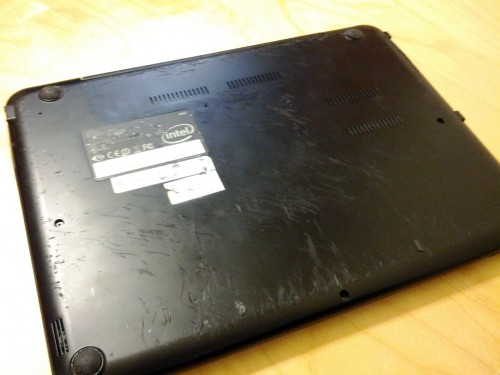 Bottom of a laptop with scratches.