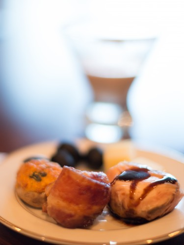 Stuffed mushroom, bacon-wrapped scallop, and prosciutto-wrapped fig on a plate with black olives, in front of a martini glass