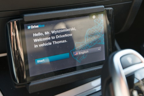 LCD screen with text: Hello, Mr. Wyszomierski, Welcome to DriveNow in vehicle Thomas.